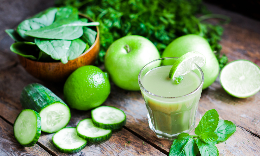 Cup of green juice with various healthy ingredients
