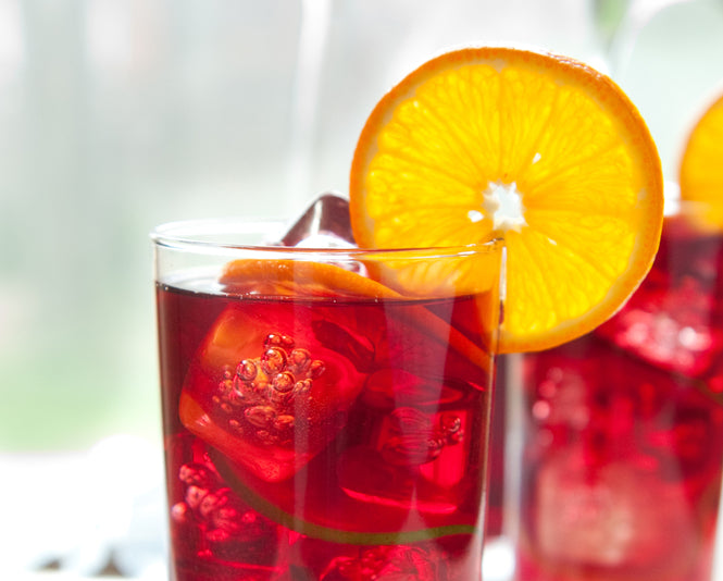 Cup of hibiscus iced tea with an orange slice