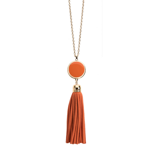 Orange suede tassel necklace with gold accents and enamel disk for monogramming.