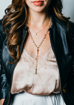 woman wearing beaded y necklace with satin top and leather jacket