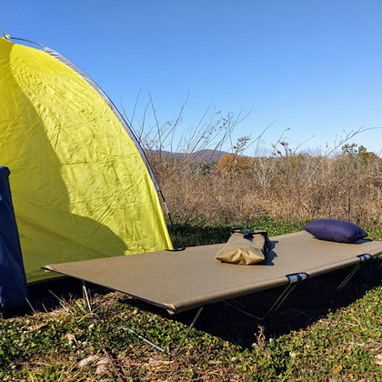 GO-KOT Camping Cot and Snugpak Travel Pillow near green tent in a field.