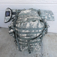 Camo backpack on the ground with a GO-KOT tactical cot strapped to it