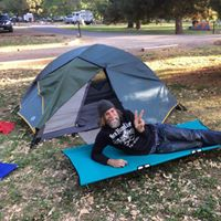 Man outside on a blue GO-KOT camping cot bed giving the peace sign