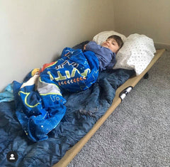 Child napping in parent's office on a GO-KOT portable cot bed