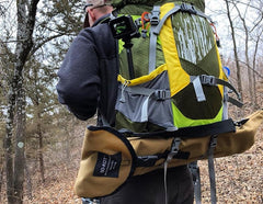 Male hiker in the woods with a backpack loaded with a GO-KOT heavy duty cot