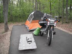 Motorcycle camp site with a motorcycle, tent, and GO-KOT motorcycle camping cot