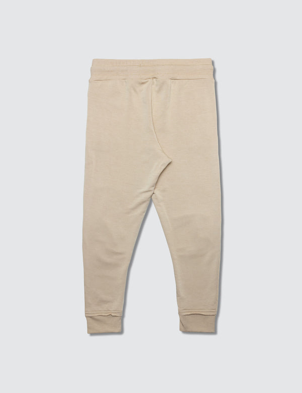 Tan sweatpant made out of recycled bamboo with two darts on the front of the knee with a non functional drawstring for kids safety