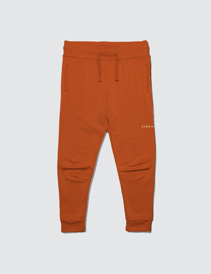 Orange sweatpant made out of recycled bamboo with two darts on the front of the knee with a non functional drawstring for kids safety