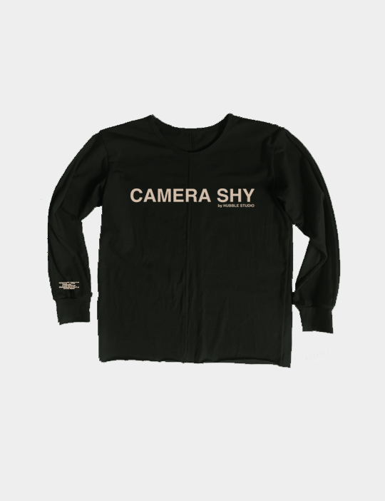 Black crewneck long sleeve tee with the words Camera Shy printed on the front.