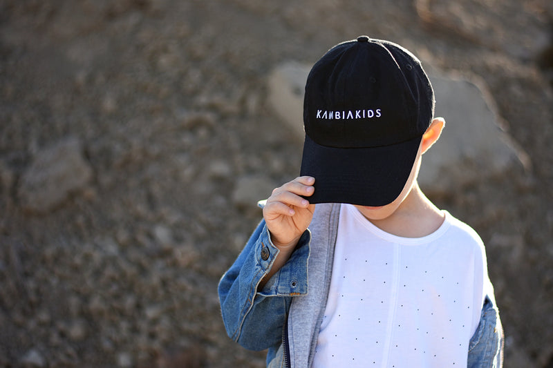 Black dad hat with the Kambia Kids logo on the front