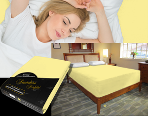 Lady in bed on stretch sheet in color 24-Sun, bed with deep mattress with Jersey knit stretch sheet in color 24-Sun