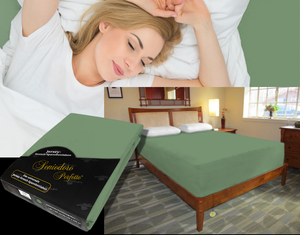 Lady in bed on stretch sheet in color 30-Sage, bed with deep mattress with Jersey knit stretch sheet in color 30-Sage