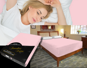 Lady in bed on stretch sheet in color 34-Rosé, bed with deep mattress with Jersey knit stretch sheet in color 34-Rosé