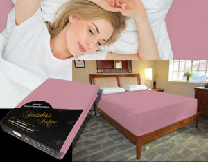 Lady in bed on stretch sheet in color 35-Old-Rose, bed with deep mattress with Jersey knit stretch sheet in color 35-Old-Rose