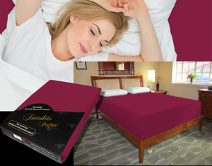 Lady in bed on stretch sheet in color 56-Bordeaux, bed with deep mattress with Jersey knit stretch sheet in color 56-Bordeaux