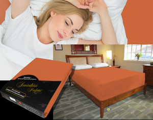 Lady in bed on stretch sheet in color 52-Terracotta, bed with deep mattress with Jersey knit stretch sheet in color 52-Terracotta