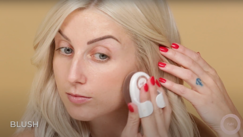 Young woman applying blush with a makeup sponge