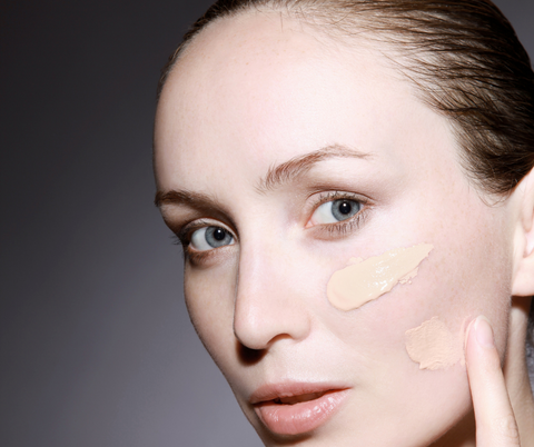 A woman demonstrating how to apply foundation by adding blobs to the main areas of her skin