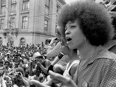 Angela Davis speaking at a Black Civil Rights Rally, sporting Black afro hair as a symbol of Black beauty