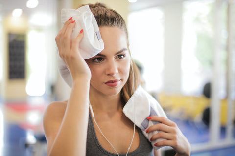 A woman using a towel to wipe her face instead of her fingers