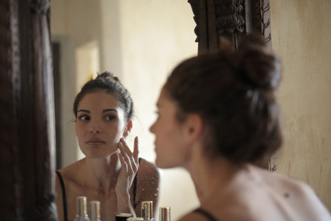 A woman touching her skin while looking in the mirror