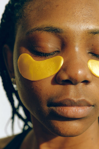 A woman with her eyes closed while using under eye masks to hydrate her skin