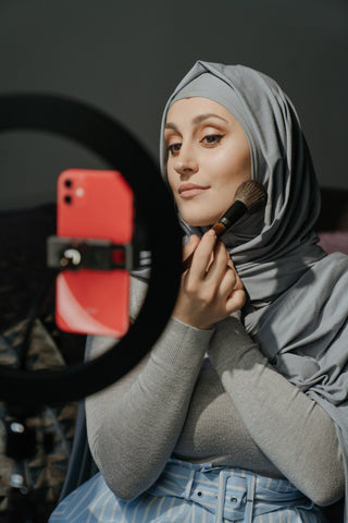 A woman applying her makeup powder for a flawless finish