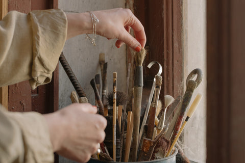 A woman tossing overly stained brushes