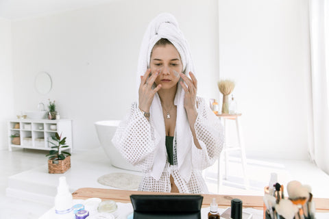 A woman with a towel over her hair practicing her skin care routine