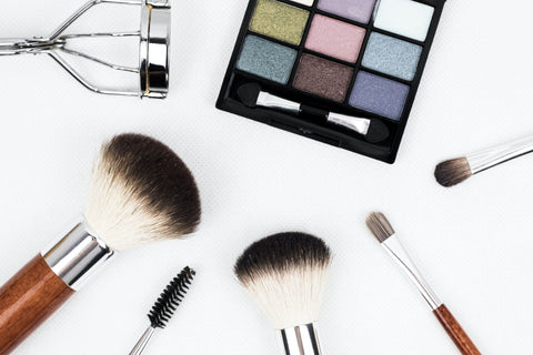 An array of makeup tools including different sized brushes, an eyelash curler, and a mascara wand