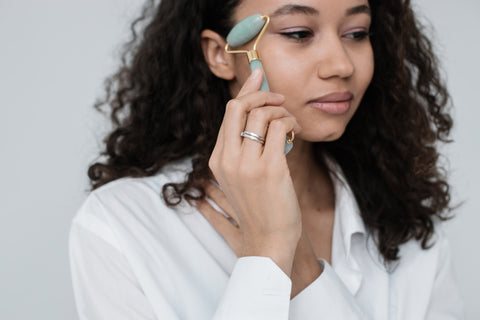 A woman using a jade roller skin care tool on her face