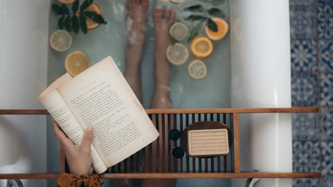 A woman practicing self care by reading a book in the bath
