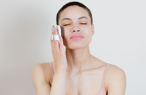 A woman using a makeup brush instead of her fingers to apply makeup to her face
