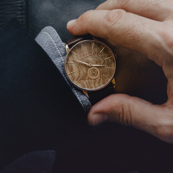 A man's wrist wearing Grundstof's Olive Burl wood watch from Wald collection