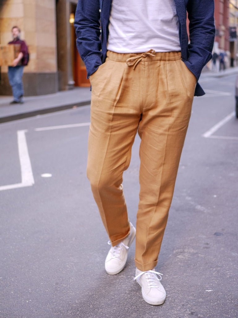 Close_Up_Of_Caramel_Irish_Linen_Drawstring_Trousers_with_Suede_Yogurt_White_Sneakers_51_Label