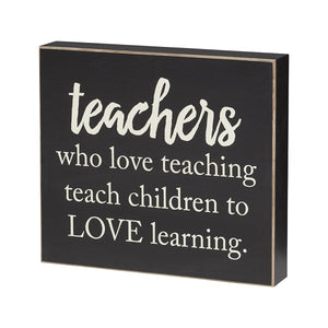"Wooden box sign painted black with white lettering that reads ""Teachers Who Love Teaching Teach Children To Love Learning""."