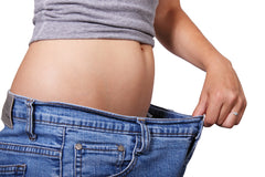 woman pulling at pants waist to show weight loss