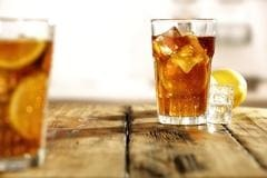 Two glasses of iced tea with lemon sitting on a wooden table top in the sun