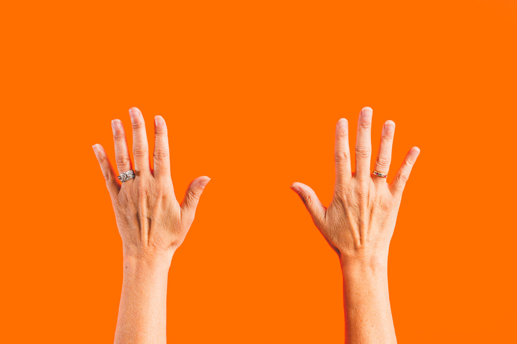 two hands reaching up on an orange background