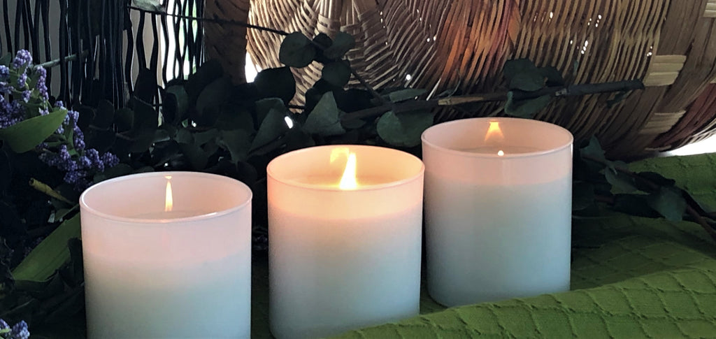 three lit white candles on a green tablecloth