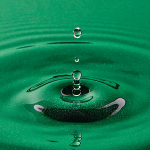 drop of water falling into a pool of green water