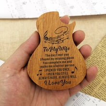 The guitar-shaped wooden box in hand is engraved with meaningful love messages for wife