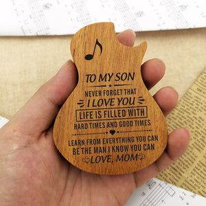 The guitar-shaped wooden box in hand is engraved with meaningful love messages for son