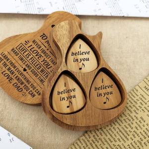 Three guitar picks with meaningful love messages for son are inside the guitar-shaped wooden box
