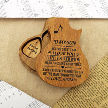 The guitar-shaped wooden box cover is stack-up on the case, and the engraved guitar pick is inside