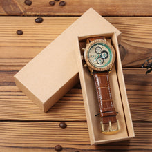 A engraved watch with brown leather band is inside a rectangle watch box