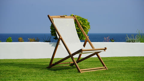 A lawn chair sitting on artificial grass in front of the beach