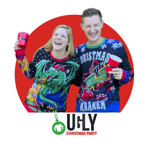 couple drinking and laughing while wearing ugly Christmas sweaters, she in one with a green dragon and fire up the sleeves, he in one that says Christmas Kraken and shows a kraken attacking Santa's sleigh