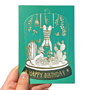 Green birthday card with gold detail featuring an acrobat in a belljar
