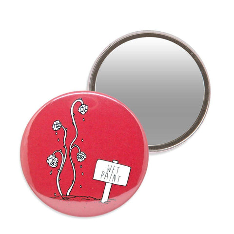 Red makeup mirror with an illustration of painted roses from Alice in Wonderland